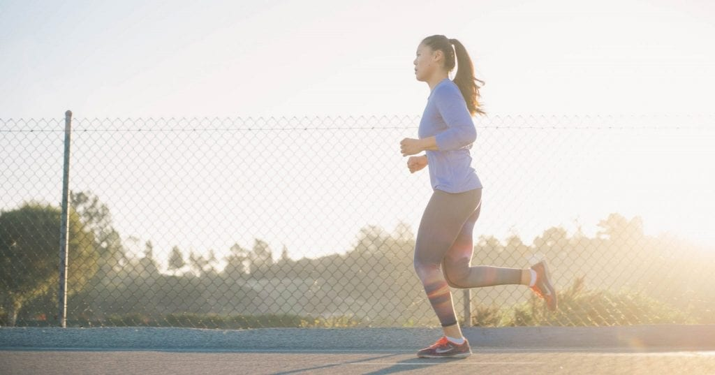Woman running on street at sunset