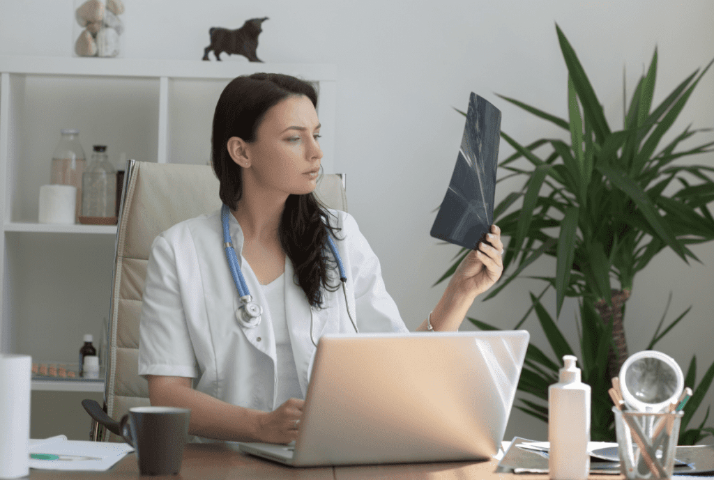 Young female veterinarian looking at x-ray in her office