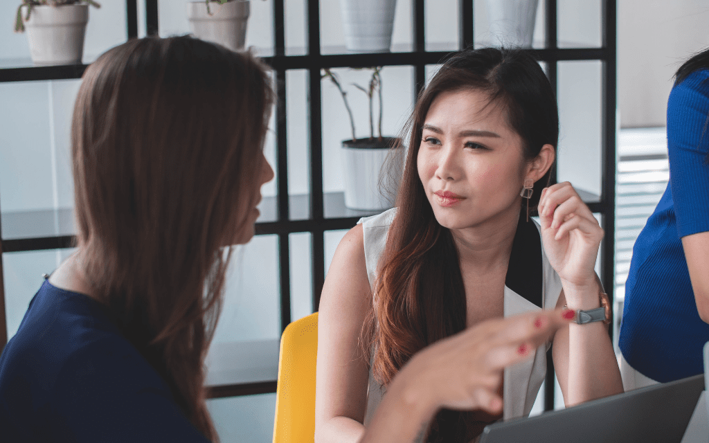 Young Asian woman listening to coworker