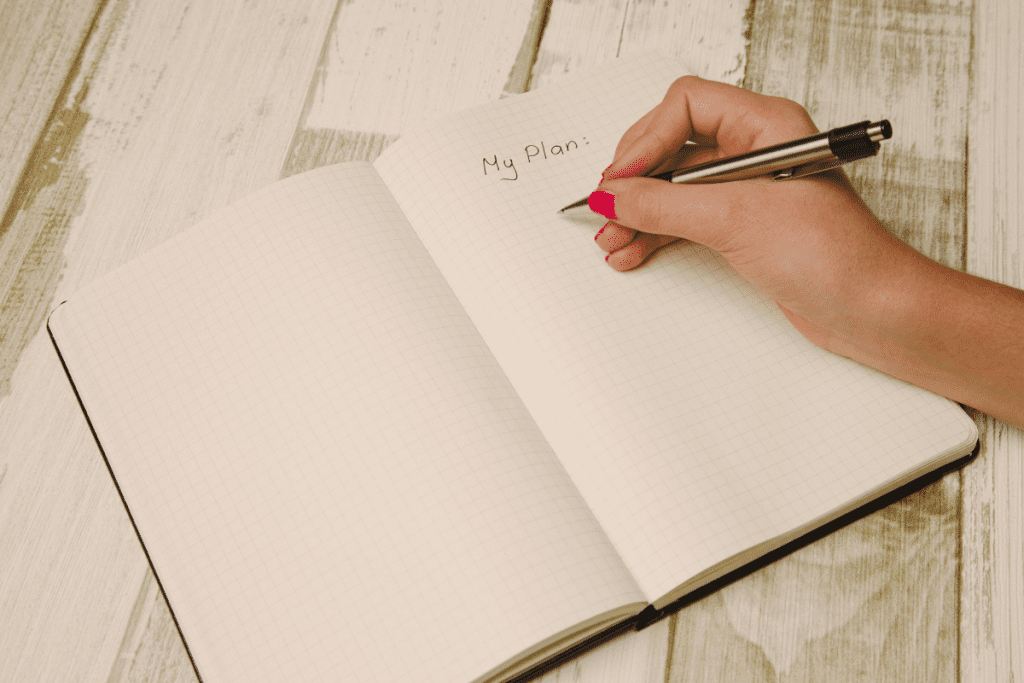 Hand writing plan in notebook