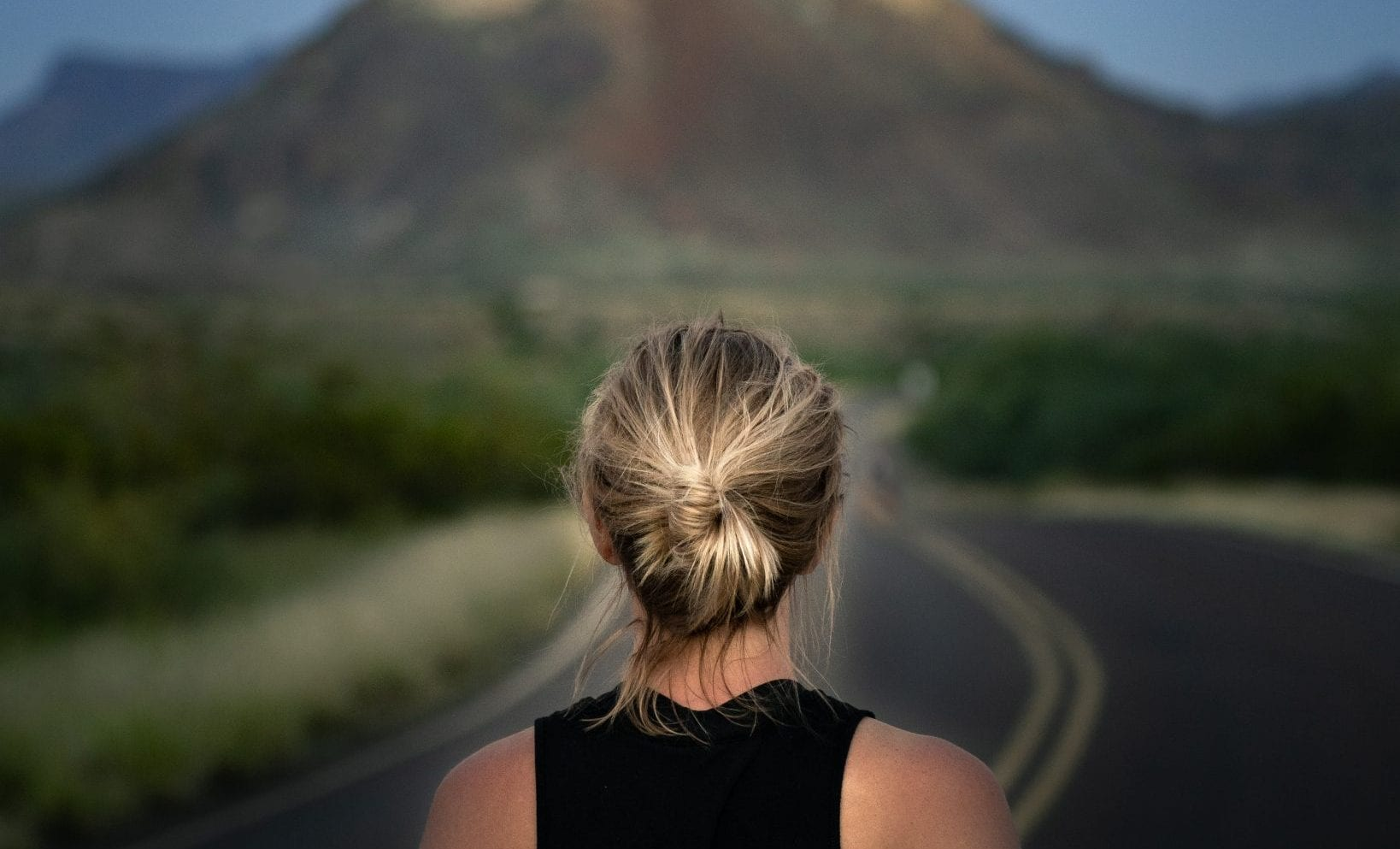 Woman stares at mountain at end of road