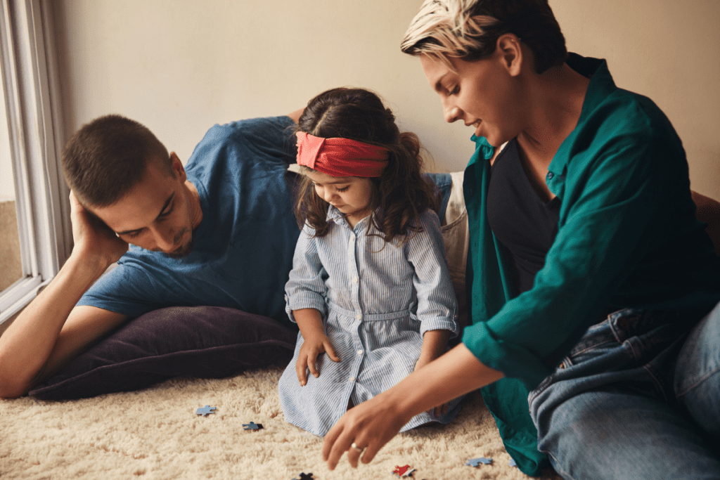 Young daughter doing puzzle with parents on carpet