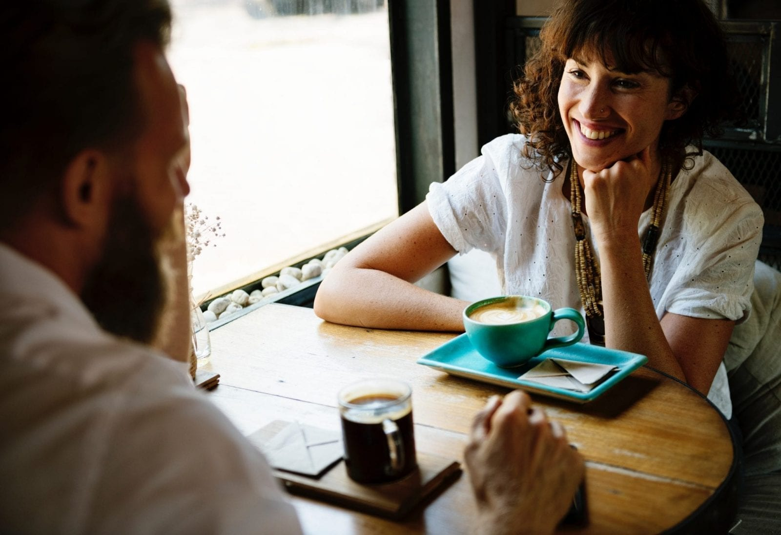 Two people talking and smiling in coffee shop