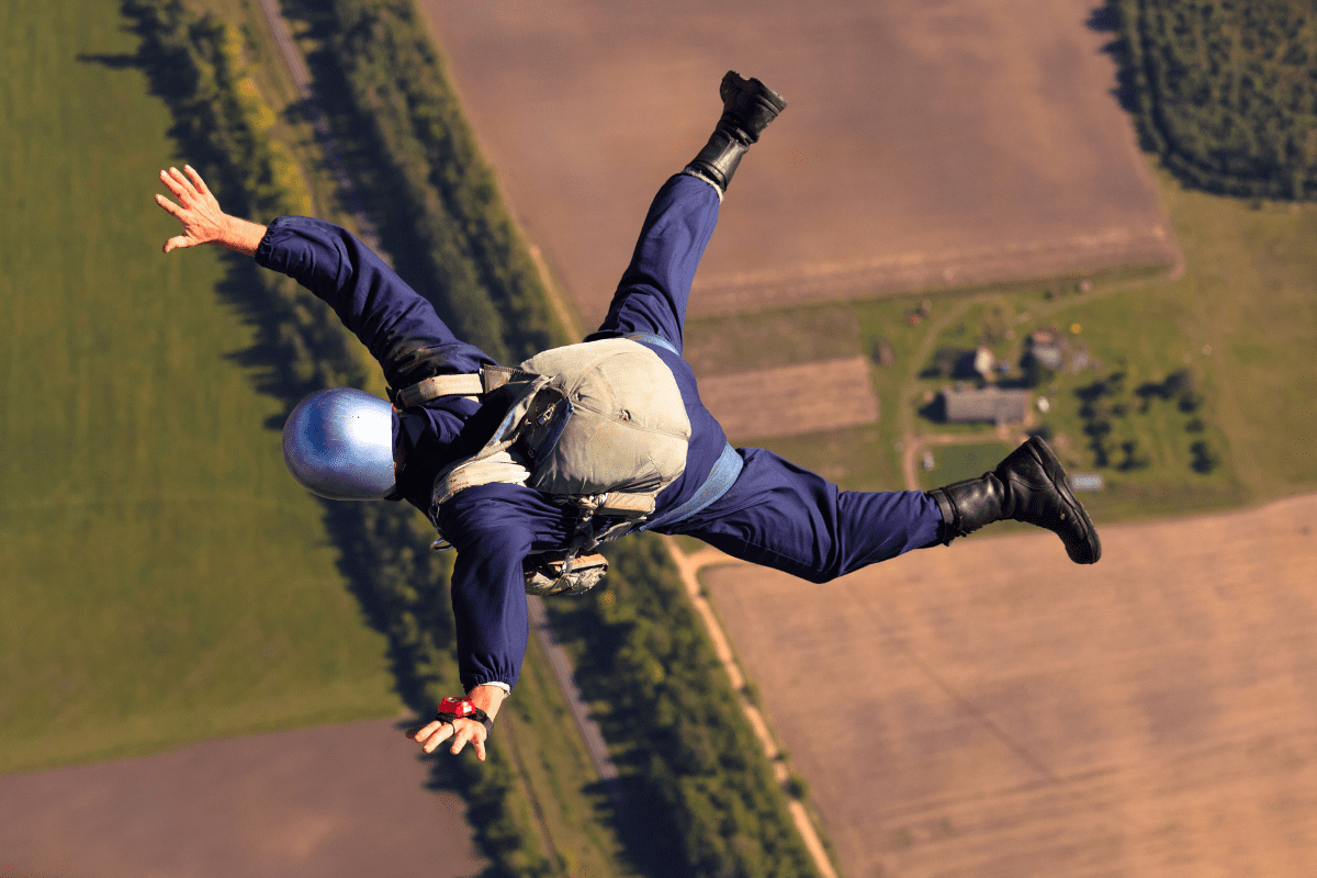 man skydiving over farmland