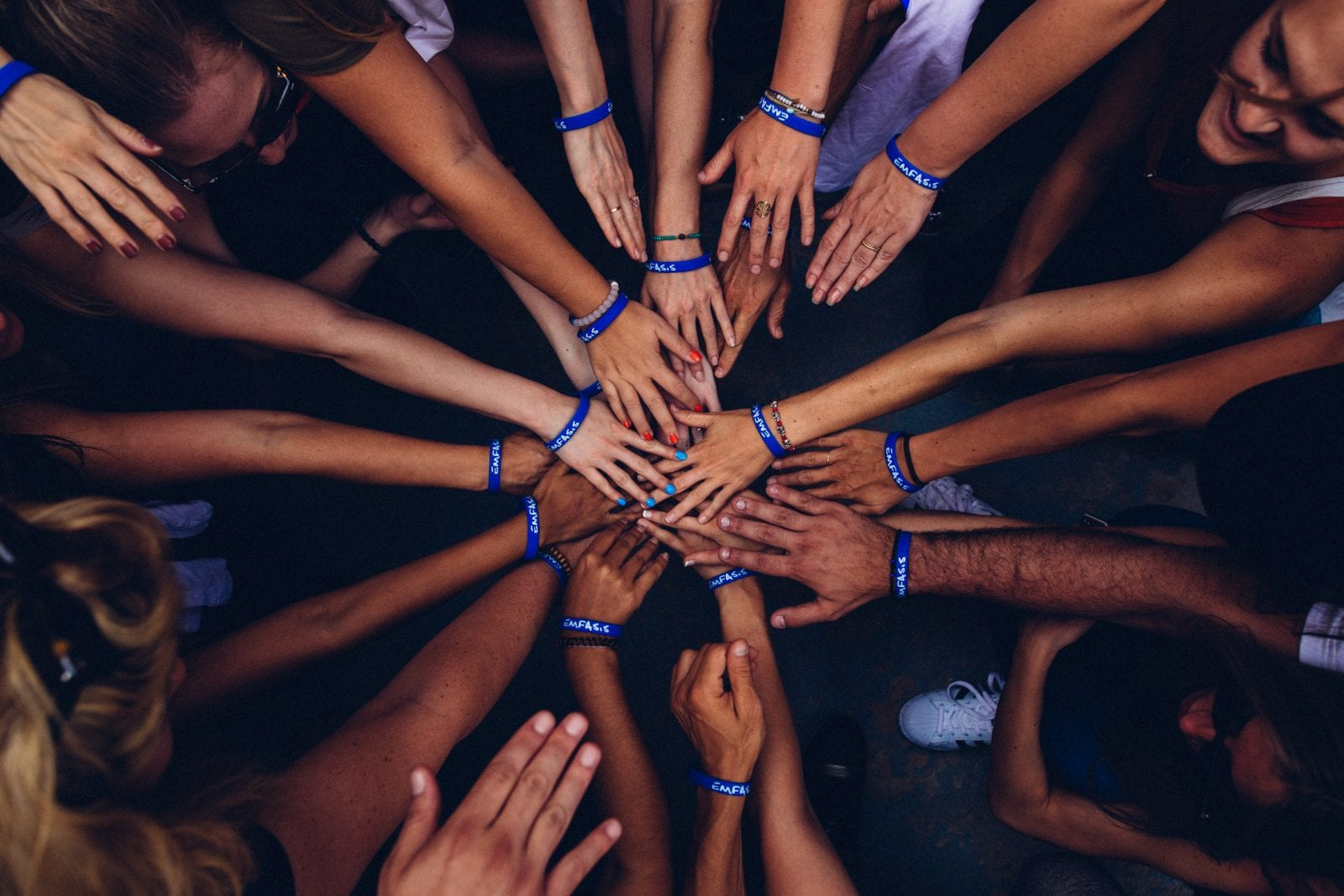 group of people putting hands into a huddle