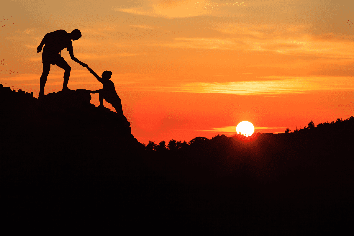 sunset picture of hiker helping another person up