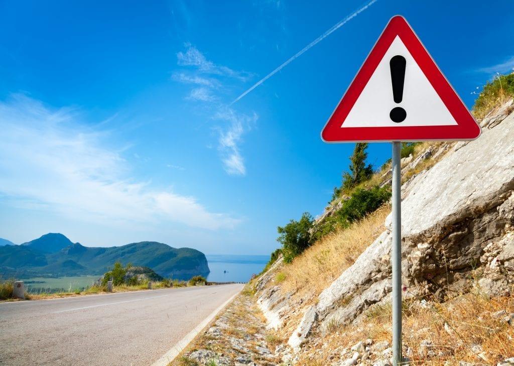 warning sign beside street