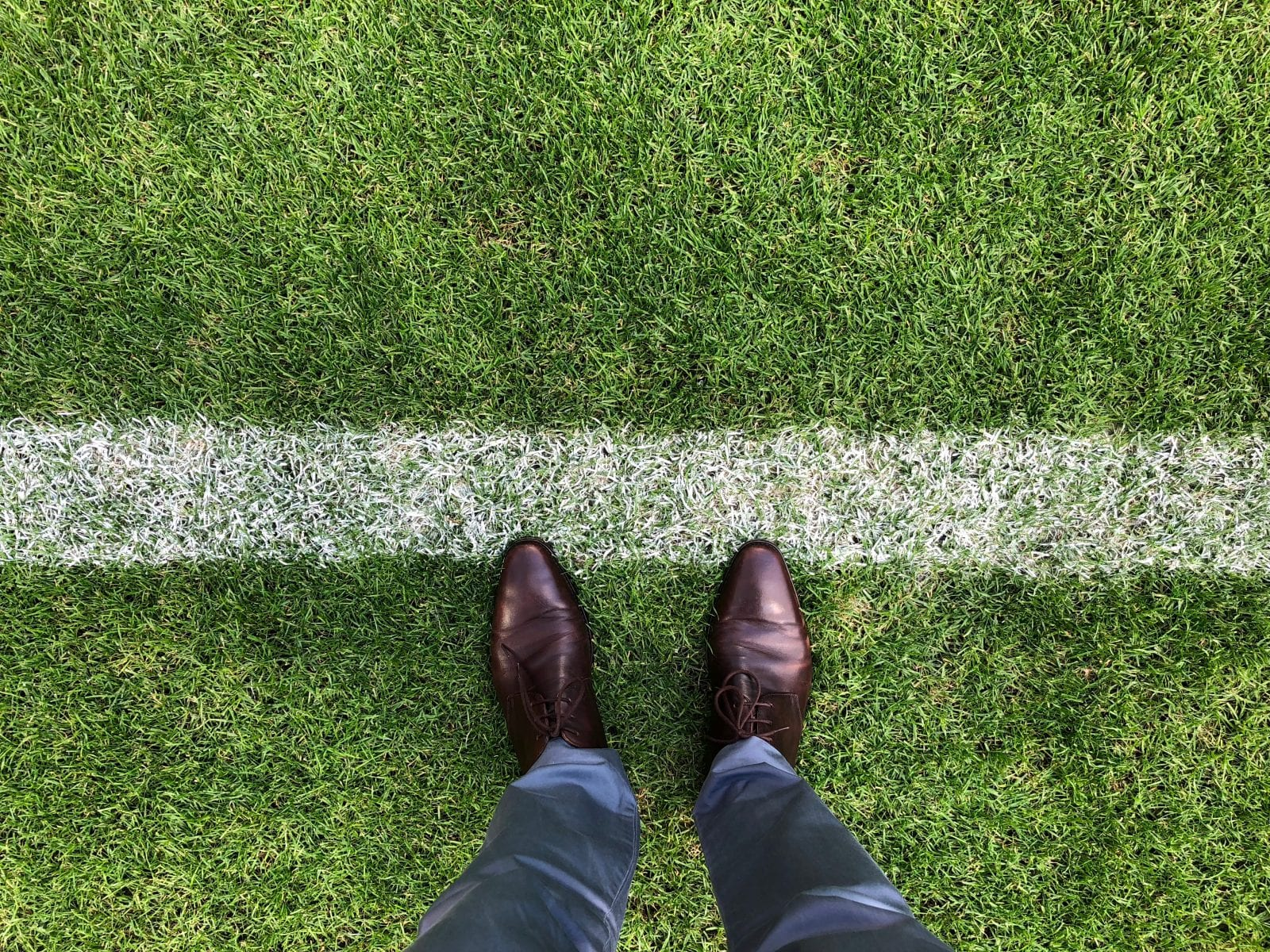 chalked line in grass with standing feet